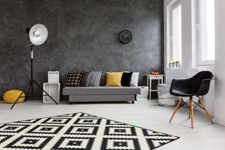 Moderne woonkamer met grote ruimte in het midden. Tegen de muur comfortabel grijze bank met kussens en zwarte stoel