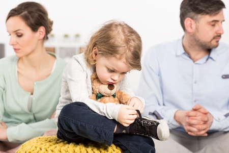 Foto van een sombere jong gezin met een droevige kleine bou knuffelen een teddy beer en zijn ouders met depressieve looks Stockfoto