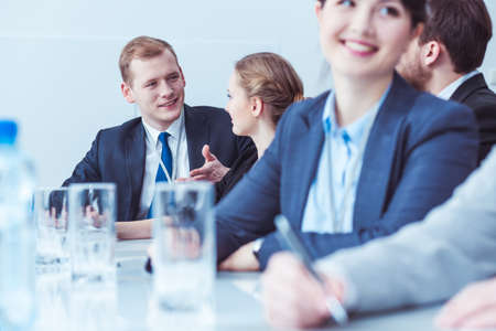 color consultation: Management of business company meeting in office. Young handsome man talking with his pretty colleague Stock Photo