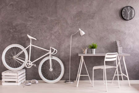 vintage living room: White vintage bicycle and desk in modern designed living room with grey wall