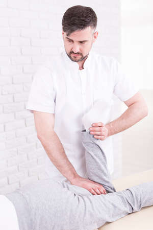 hurtful: Young handsome experienced physiotherapist doing passive exercises with his sick patient Stock Photo