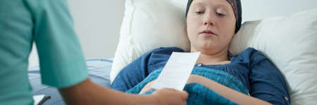 malignant neoplasm: Doctor giving cancer patient prescription during home visit