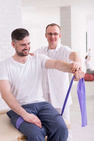 elastic band: HAppy middle aged man exercising with physiotherapist in his cabinet. Man stretching elastic band with his arm Stock Photo