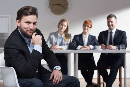 traineeship: Picture of a smiling businessman and his colleagues in a background