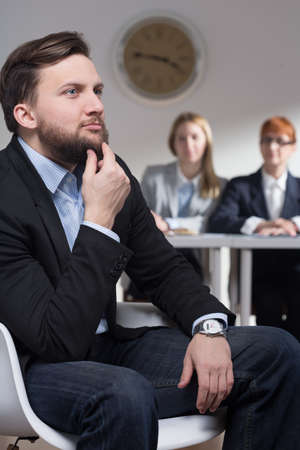 traineeship: Shot of a thoughtful businessman and his colleagues in a background