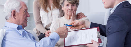 Notary giving testament and pen to his ill senior client, young woman embracing sad senior woman