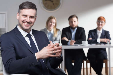 traineeship: Shot of a smiling businessman and his colleagues