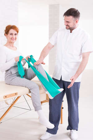elastic band: Smiling aged woman on rehabilitation sitting on a table and flexing her leg with elastic band. Next to her experienced therapist