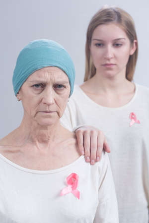 fighting cancer: Shot of two women wearing pink ribbons, an international symbol of breast cancer awareness