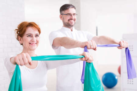 elastic band: Happy aged woman exercising with elastic band. Next to her training middle aged physiotherapist