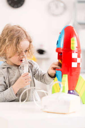 Child with cystic fibrosis using nebulizer, playing with toy racket Stock Photo
