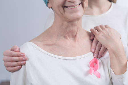 fighting cancer: Cropped picture of a sick woman wearing a pink ribbon