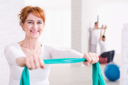 hurtful: Senior happy pretty woman exercising in physiotherapists office. Stretching elastic band with arms