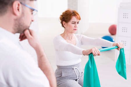 hurtful: Senior tired woman exercising her arms with elastic band with big effort. Next to her therapist watching her training