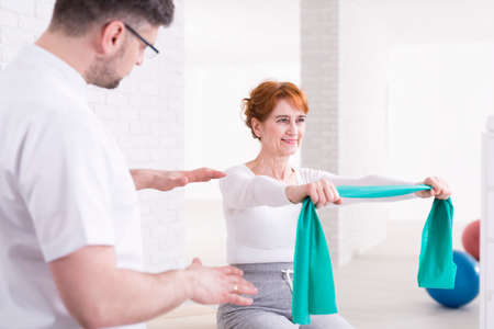 Young physiotherapist helping his senior patient to exercise her arms with elastic band Stock Photo