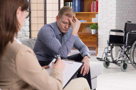 color consultation: Broken down young man on psychotherapy session after accident. In the background mans wheelchair Stock Photo