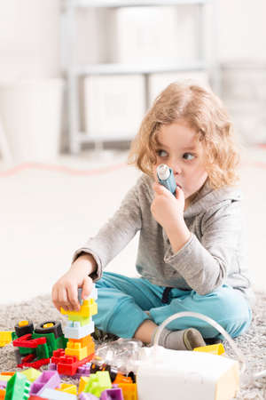 asthmatic: Small girl using inhaler device, playing with toys on a floor