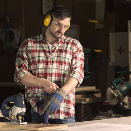 well equipped: Professional carpenter during work in well equipped workshop