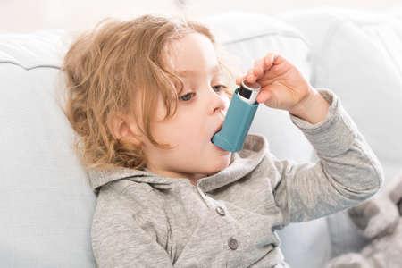 Niño pequeño usando su dispositivo inhalador para el asma