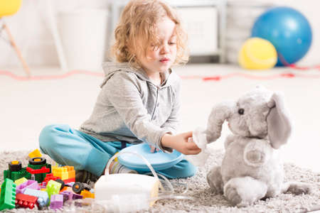 dust mask: Small child playing with toy elephant, asthma treatment device lying on a floor