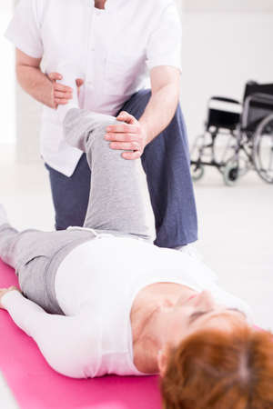 hurtful: Elderly woman after spinal cord injury exercising passive exercises with her physiotherapist Stock Photo
