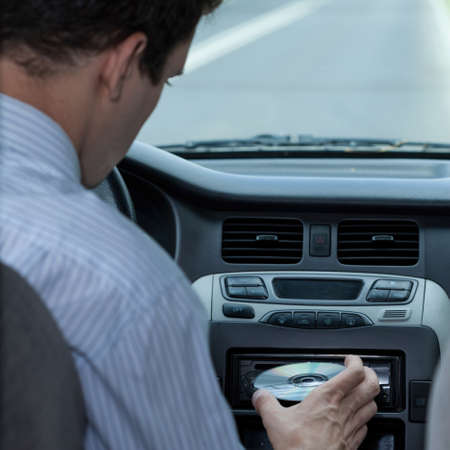 distraction: A driver inserting a CD in the car Stock Photo