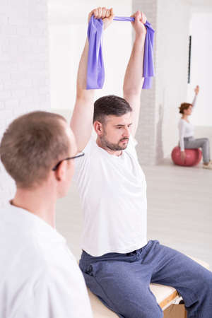 physiotherapists: Strong young man sitting on a treatment table at physiotherapists cabinet. Trying to stretch elastic band in arms Stock Photo
