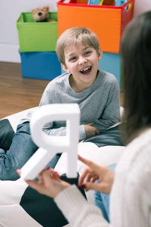Schot van een logopedist en een gelukkig jongetje
