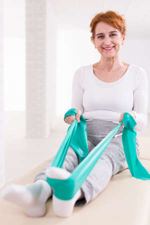 hurtful: Happy elderly pretty woman in physiotherapists office sitting on a treatment table. Strengthening her legs with elastic band Stock Photo