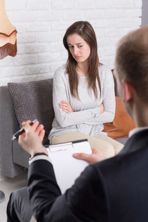 traumatic: Pretty young concerned woman afraid to talk with psychotherapist after traumatic accident during her session