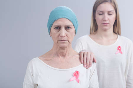 fighting cancer: Picture of mother and daughter wearing pink ribbons, an international symbol of breast cancer awareness