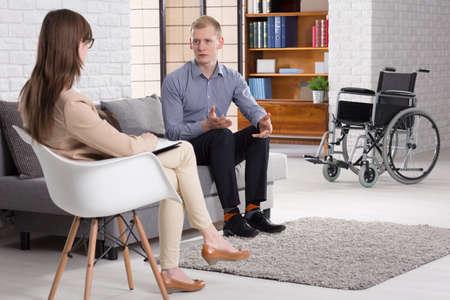 medula espinal: joven de lesionados con una lesión de la médula espinal hablando de accidente con el joven psicoterapeuta