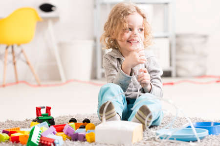 asthmatic: Small girl doing inhalation, sitting on a floor among toys in light interior