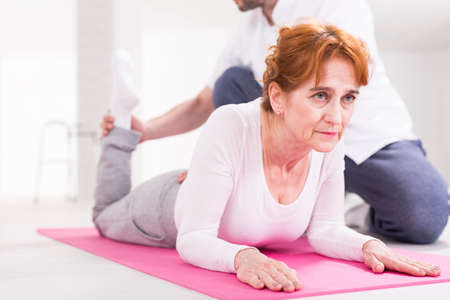 hurtful: Focused senior active woman exercising during rehabilitation after injury. Next to her physiotherapist helping with training Stock Photo