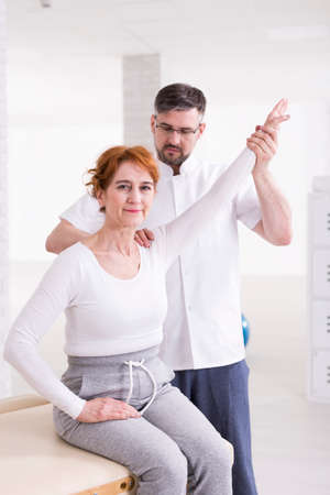 hurtful: Older pretty woman with arm pain treating at physiotherapists cabinet. Young man in uniform holding womans arm Stock Photo