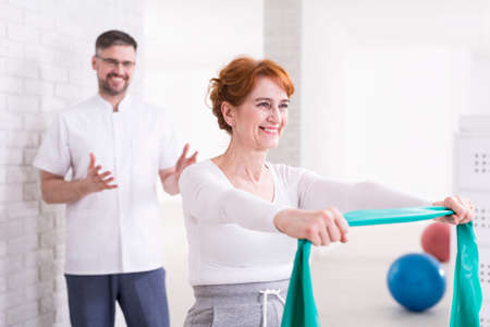 hurtful: Smiling elderly woman in tracksuit exercising her arms with elastic band. Behind her happy young physiotherapist proud of his patient Stock Photo