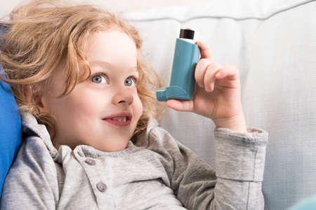 asma: Pequeño muchacho sonriente que sostiene el inhalador, sentado en un sofá luz Foto de archivo
