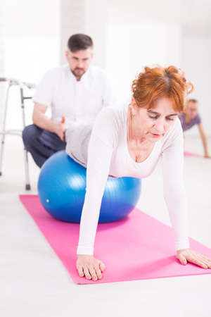 hurtful: Senior active woman exercising on a big ball at physiotherapists cabinet. Young therapist helping woman to keep stability
