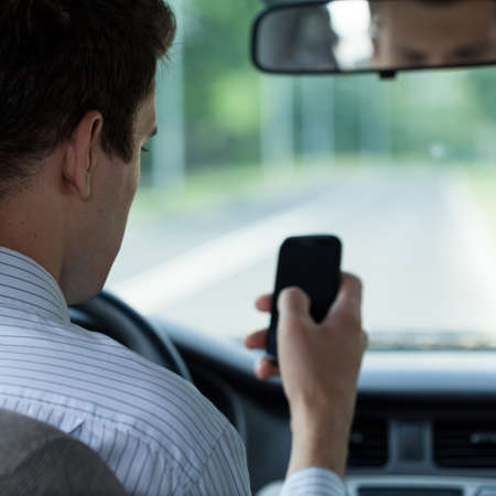 dissociation: Horizontal view of driver using mobile phone Stock Photo