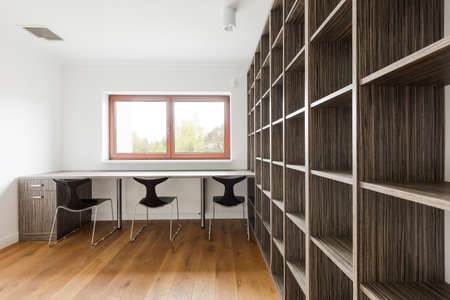 interior spaces: Light interior with window, long desk, chairs and big wooden shelving unit Stock Photo