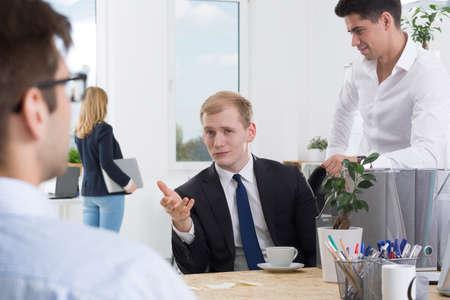 demanding: Demanding client in elegant suit during meeting with two graphic designers, light interior
