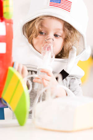 cystic fibrosis: Child in an astronaut costume using a nebulizer, playing with a toy racket Stock Photo