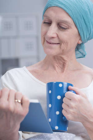 fighting cancer: Shot of a sick woman after chemotherapy reading a book Stock Photo