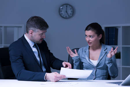 work team: Stressed businesswoman and her angry boss sitting in office at night