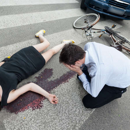 girl lying: A dead woman lying on the road and a driver crying Stock Photo