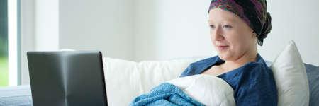 leucemia: chica del cáncer usando la computadora portátil en la cama sonriendo Foto de archivo