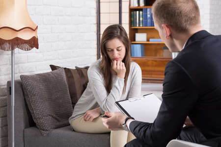 color consultation: Young elegant man talking with his worried patient during session in office. Young woman afraid to talk
