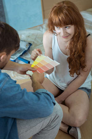 redecoration: Shot of a young couple sitting on a floor and choosing a colour from a colour swatch Stock Photo