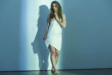 mujer golpeada: mujer maltratada joven de pie descalzo por una pared blanca en una habitación vacía con una mirada de desesperación en su cara