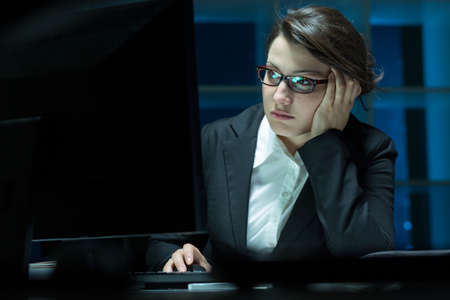 working late: Overworked businesswoman sitting beside desk, using computer, working at night Stock Photo